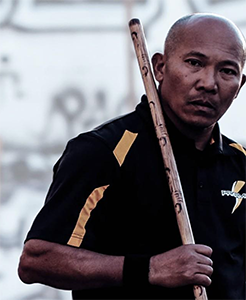 Grandmaster Roiles seen looking stern with a fighting stick resting on his shoulder.